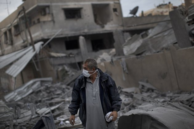 a-palestinian-man-walks-among-debris-after-an-israeli-airstrike-at-hamas-prime-minister-ismail-haniyehs-office-right-in-gaza-city-saturday-nov-17-2012-israel-bombarded-the-hamas-ruled-gaza-strip-with-more-than-180-airstrikes-early-saturday-widening-a-blistering-assault-on-militant-operations-to-target-government-and-police-compounds-and-a-vast-network-of-smuggling-tunnels