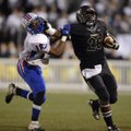 Tearris Wallace, right, a Bentonville running back, stiff-arms West Memphis defensive back Calman Cl...