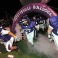 Fayetteville High School players take the field Friday before the Bulldogs' playoff game with Conway...