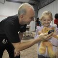 Rowdy Gaines, a 1984 Olympic gold medal swimmer, visits Friday with Leanne Jacobson, 9, of Rogers af...