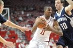 NWA Media/ANDY SHUPE -- Arkansas sophomore guard BJ Young, center, drives to the lane past Longwood freshman forward Karl Ziegler (20) Sunday, Nov. 18, 2012, during the first half of play in Bud Walton Arena.