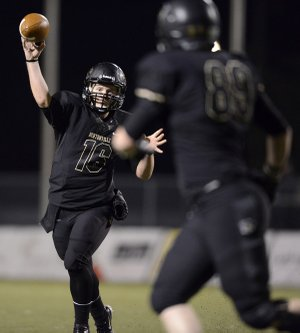 Reese Dollins, left, Bentonville's quarterback, passes the ball to tight end Chase Morse on Friday during the Tigers' Class 7A playoff game at Tiger Stadium in Bentonville.