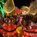 Parade floats make their way around the Fayetteville square Saturday during the annual lighting cere...