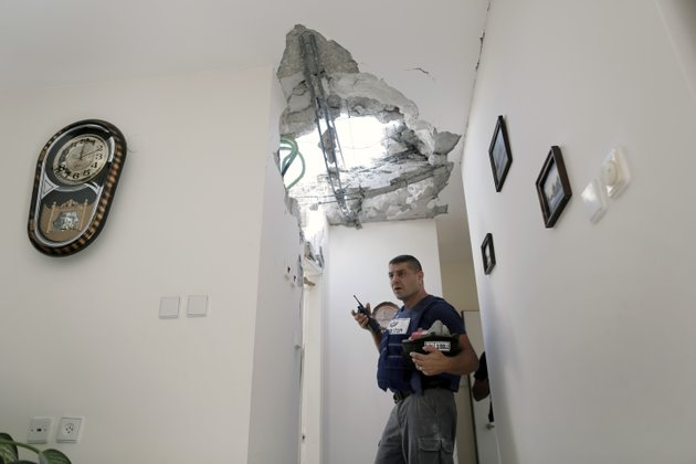 an-israeli-police-officer-stands-inside-a-damaged-house-after-a-rocket-fired-by-palestinian-militants-from-gaza-strip-landed-in-ashkelon-southern-israel-sunday-nov-18-2012-israel-launched-the-operation-last-wednesday-by-assassinating-hamas-military-chief-and-carrying-out-dozens-of-airstrikes-on-rocket-launchers-and-weapons-storage-sites-over-the-weekend-the-operation-began-to-target-hamas-government-installations-as-well-including-the-offices-of-its-prime-minister