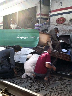 Distraught Egyptians search for loved ones Saturday in the wreckage of a train that crashed into a bus carrying children to a kindergarten near Assiut, Egypt. At least 50 people, most of them children, were killed.