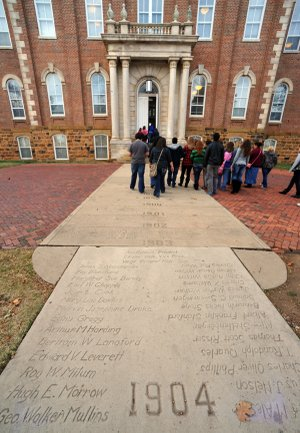 Visitors look at names on the Senior Walk in front of Old Main on the University of Arkansas campus in Fayetteville on Monday.