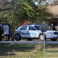 Benton County Prosecutor Van Stone and Bentonville police investigators stand outside a house on Sou...
