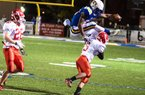 North Little Rock running back Altee Tenpenny jumps over Cabot defensive back Jordan Burke during the Charging Wildcats' 28-0 victory in the Class 7A quarterfinals Friday night in North Little Rock. Tenpenny, who rushed for 141 yards in Friday's victory, was penalized on the play for hurdling.