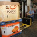 Dennis Morris (above) with Northwest Arkansas Food Bank loads a truck on Tuesday with food items for...