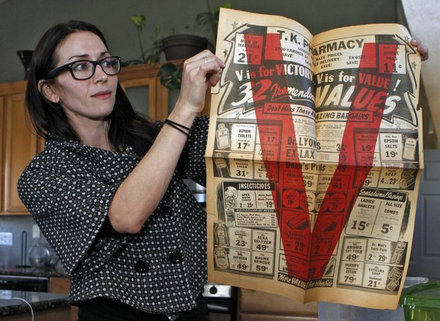 in-this-photo-taken-tuesday-nov-20-2012-alissa-williams-holds-up-a-an-advertising-flyer-from-tk-pharmacy-at-her-home-in-denver-the-flyer-from-the-early-1940s-was-found-with-other-documents-and-letters-during-renovations-at-a-former-denver-pharmacy-owned-by-japanese-americans