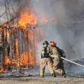 Shawn Rogers, left, and Aaron Box, Rogers firefighters, extinguish a storagebuilding fire Tuesday ne...