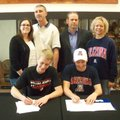 Lane Brand, seated left, and Gage Crosby, Bentonville swimmers, sign their national letters of inten...