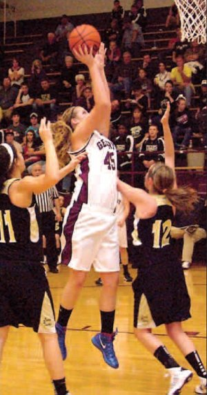 Surrounded by West Fork defenders, Gentry's center, Heather Marshall, puts in a quick jump shot for two in an earlier home game. Marshall helps the Lady Pioneers dominate under the basket.