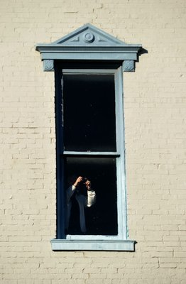 Photo by Michael Woods—                                                                                        A visitor snaps a photo from the third floor window of the old Dixieland shoe store on the corner of Walnut and 1st street in Rogers during a tour of the building Wednesday morning.  John Mack, owner of JKJ Architects, recently purchase the former Dixieland Shoe store on the corner of First and Walnut street. He is restoring the building which includes the Opera House on the second floor, once a grand theater.