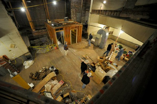 Photo by Michael Woods—                                                                                        Visitors take a look around the old opera house on the second floor of the old Dixieland shoe store on the corner of Walnut and 1st street in Rogers Wednesday morning.  John Mack, owner of JKJ Architects, recently purchase the former Dixieland Shoe store. He is restoring the building which includes the Opera House on the second floor, once a grand theater.