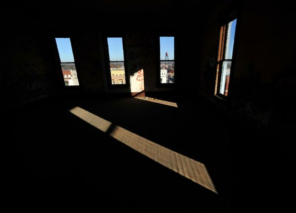 Photo by Michael Woods—                                                                                        Sunlight falls into a third floor room on the north east corner of the old opera house in the old Dixieland shoe store on the corner of Walnut and 1st street in Rogers Wednesday morning.  John Mack, owner of JKJ Architects, recently purchase the former Dixieland Shoe store. He is restoring the building which includes the Opera House on the second floor, once a grand theater.