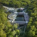 Designed by Moshe Safdie, the multiple buildings of Crystal Bridges Museum nestle seamlessly into th...