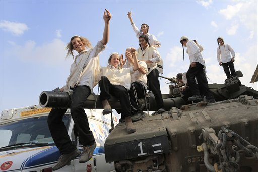 ultra-orthodox-jews-of-the-bratslav-hasidic-sect-that-gathered-to-show-support-for-the-forces-dance-as-they-celebrate-atop-of-a-tank-in-southern-israel-close-to-the-israel-gaza-strip-border-thursday-nov-22-2012-a-cease-fire-agreement-between-israel-and-the-gaza-strips-hamas-rulers-took-effect-wednesday-night-bringing-an-end-to-eight-days-of-the-fiercest-fighting-in-years-and-possibly-signaling-a-new-era-of-relations-between-the-bitter-enemies