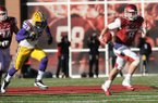 NWA Media/ANDY SHUPE -- Arkansas quarterback Tyler Wilson scrambles with the football while being pursued by LSU defensive end Barkevious Mingo (49) during the second quarter of play Friday, Nov. 23, 2012, at Razorback Stadium.