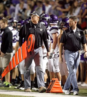 David Hook, left, and Todd Hook walk down the sideline to move the first down measuring chain and sticks during the game between Bentonville and Fayetteville on Nov. 2 at Tiger Stadium in Bentonville.