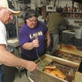 Maudie Schmitt, center, owner of Cafe Rue Orleans in Fayetteville, turns a turkey in a fryer Thursda...