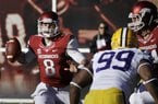 Arkansas quarterback Tyler Wilson (8) passes over LSU defensive end Sam Montgomery (99) as Arkansas offensive tackle Brey Cook, right, defends during the second quarter of an NCAA college football game in Fayetteville, Ark., Friday, Nov. 23, 2012.