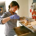 Ashley Evilsizor moves pieces of turkey to a tray at Charity Baptist Church on Thursday in Rogers. F...
