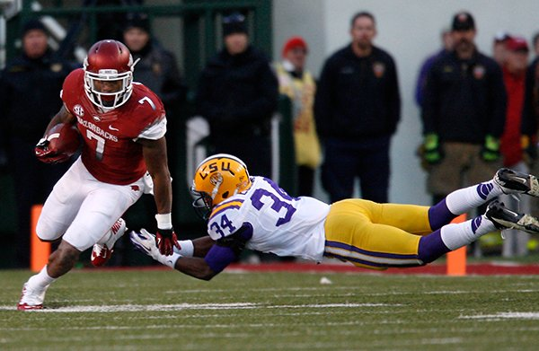NWA Media/JASON IVESTER -- Arkansas running back Knile Davis slips past a tackle attempt from LSU safety Jeremy Hill during the fourth quarter on Friday, Nov. 23, 2012, at Donald W. Reynolds Razorback Stadium in Fayetteville.