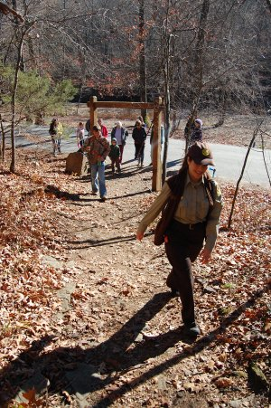 Rebekah Penny, an interpreter at Devil's Den State Park in southern Washington County, leads a hike Friday along Yellow Rock Trail. The park promoted the day as Green Friday, an alternative to Black Friday, the busiest shopping day of the year.