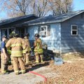 Bentonville firefighters investigate a house fire Friday at 903 S.E. A St. The fire was reported aro...