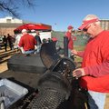 Mike Moffett of Fayetteville checks on a piece of meat he was smoking Friday while tailgating with f...