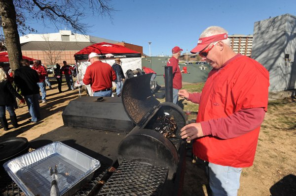 Mike Moffett of Fayetteville checks on a piece of meat he was smoking Friday while tailgating with friends before the University of Arkansas football game with Louisiana State in front of Bud Walton Arena in Fayetteville.