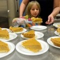 Serenity Alderson, 6 from Springdale, helps her mother, Sondra Alderson, cut pies Friday to serve fo...