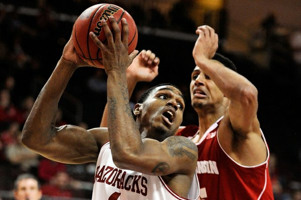 Arkansas' Coty Clarke (4) looks to make a shot with Wisconsin's Ryan Evans (5) defending during the second half of an NCAA college basketball game at the Continental Tire Las Vegas Invitational tournament on Saturday, Nov. 24, 2012, in Las Vegas. Wisconsin won 77-70. (AP Photo/David Becker)