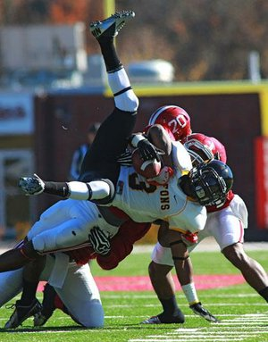 Henderson State linebacker Maxie Graham (hidden) throws down Missouri Western State wide receiver Tyron Crockom during the second half of Saturday's NCAA Division II playoff game at Carpenter-Haygood Stadium in Arkadelphia. Missouri Western won 45-21. More photos available online at arkansasonline.com/galleries.