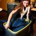 Annie Bachmayer, a Lincoln Junior High School volleyball player, works to fill bags with hygiene pro...