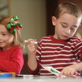 Devin Brewer, 6, right, and sister, Abby Brewer, 5, both of Fayetteville, color in holiday cards Sat...