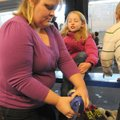 Tasha Martin, left, helps daughter Grace Martin slip on a pair of ice skates Saturday at the Jones C...