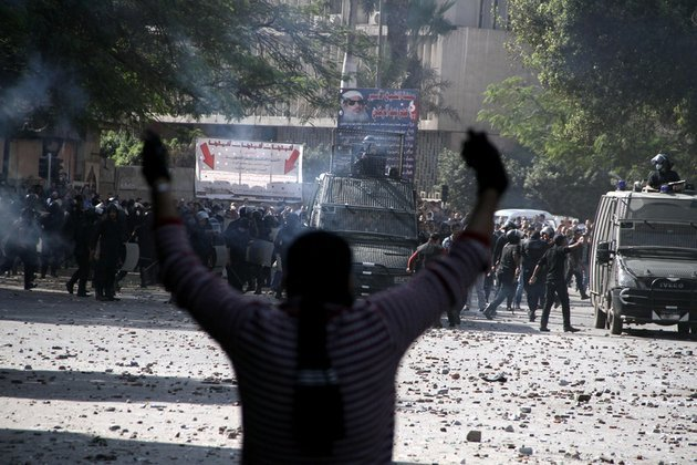egyptian-security-forces-background-clash-with-protesters-near-tahrir-square-in-cairo-on-sunday-nov-25-2012