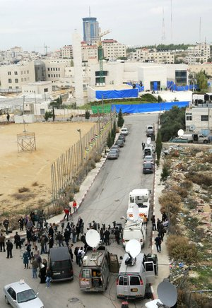 Journalists wait Tuesday on the road leading to the mausoleum of Yasser Arafat in the West Bank city of Ramallah as authorities exhume the former Palestinian leader's remains in an investigation into his death.