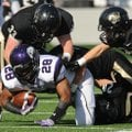 Brice Gahagans, a Fayetteville junior running back, is tackled by Bentonville linebacker Garrett Kau...