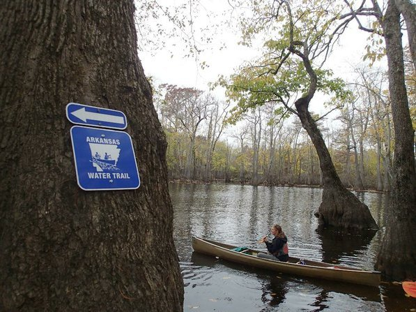 Prominent signs are placed at access areas along Arkansas Water Trails. The route is marked with small blazes that don't detract from the beauty of the swamp. Kirsten Bartlow heads out from the Lake Hickson access along Bayou De View.