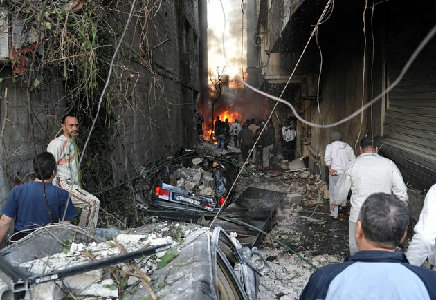 in-this-photo-released-by-the-syrian-official-news-agency-sana-syrian-citizens-gather-at-an-alley-destroyed-by-two-cars-bombs-in-the-jaramana-suburb-of-damascus-syria-on-wednesday-nov-28-2012
