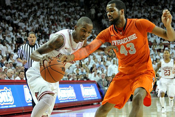 NWA Media/MICHAEL WOODS -- 11/30/2012-- Arkansas guard BJ Young tries to get past past Syracuse defender James Southerland during the first half of Friday night's game at Bud Walton Arena in Fayetteville