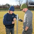 Ferguson, (left) right, assists Henson install poles in outfield at Veterans Park.