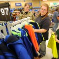Gena Whittenburg, center, of Fayetteville, helps her son Tobey, 6, pick out a new hoodie Friday with...