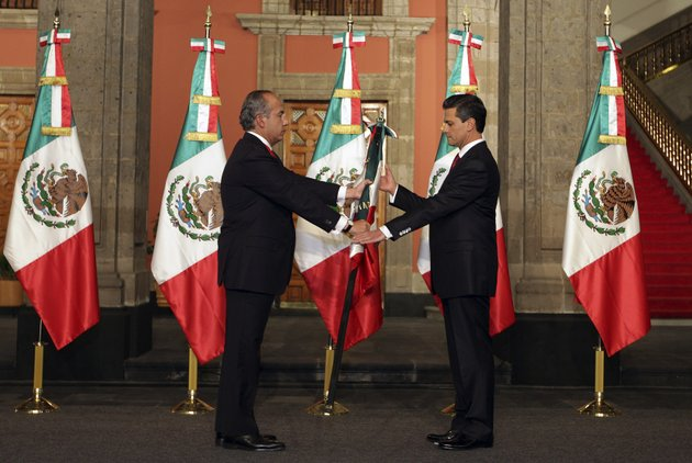 in-this-image-released-by-the-press-office-of-president-elect-enrique-pena-nieto-on-saturday-dec-1-2012-mexicos-outgoing-president-felipe-calderon-left-gives-a-mexican-flag-to-president-elect-enrique-pena-nieto-during-the-official-transfer-of-command-ceremony-at-the-national-palace-in-mexico-city-saturday-dec-1-2012-pena-nieto-will-be-officially-sworn-in-as-mexicos-new-president-during-a-ceremony-at-the-national-congress-later-on-saturday