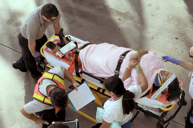 emergency-personnel-attend-to-injured-passengers-after-a-bus-accident-at-miami-international-airport-on-saturday-dec-1-2012-in-miami-officials-say-a-bus-has-hit-an-overpass-killing-at-least-one-person-and-injuring-more-than-two-dozen-people-on-board-airport-spokesman-greg-chin-says-the-large-white-bus-hit-the-overpass-going-into-the-airports-arrivals-section-on-saturday-morning-the-bus-was-going-about-20-mph-when-it-clipped-the-roof-entrance
