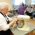 Kaye Burns adds eggs to cookie dough Friday while leading a cooking demonstration of Christmas hors ...