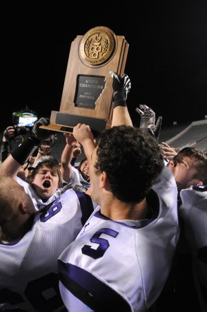 Players hoist the 7A football state championship trophy Saturday, after Fayetteville High repeated as state champions at War Memorial Stadium in Little Rock. Fayetteville beat Bentonville High School, 31-20.